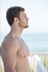 shirtless man looking off by the ocean