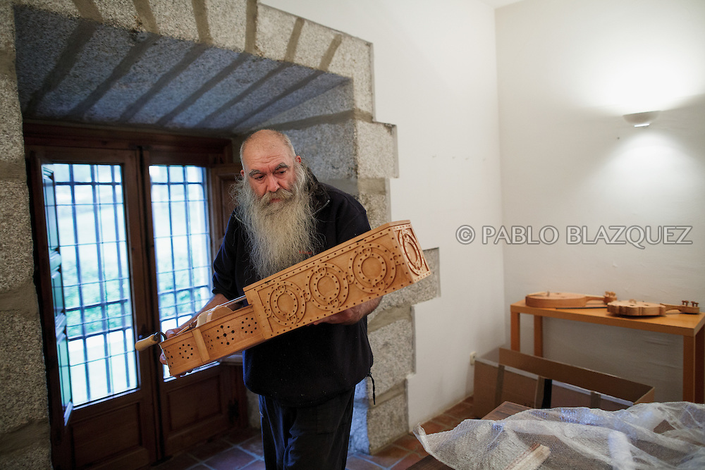 02/12/2016. Jesus Reolid carries an organistrum as he prepares an exhibition of musical instruments from medieval times recently made by luthiers at the Santa María la Real de Valdeiglesias Monastery on December 2, 2016 in Pelayos de la Presa, Madrid province, Spain. The Collegiate of Santa María la Mayor is a Romanesque architecture church built during the 12th and 13th centuries. Recents restorations of the Church discovered many details on its sculptures. Then luthiers started the project 'De la piedra a la madera' to recover and to reproduce the instruments displayed on the North Gate. (© Pablo Blazquez)