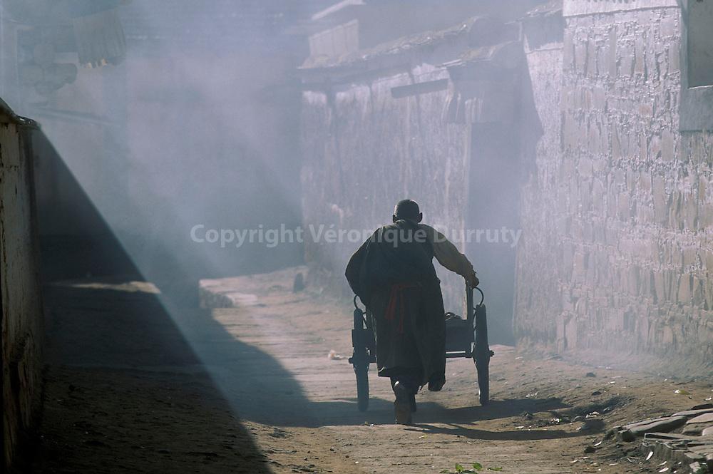 Homme de la communauté tibétaine de Xiahe poussant un chariot à bras...Man from the tibetan community of Xiahe