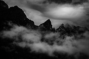 Dolomites from Molveno, Italy. A black and white photograph of a mountian range with gathering clouds at dusk.