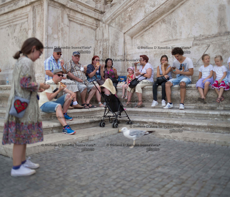 turisti pranzano seduti sui gradini del campidoglio roma,<br />