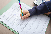 Close-up of girl's hand writing on paper