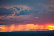 Rain pours through the storn clouds at sunset