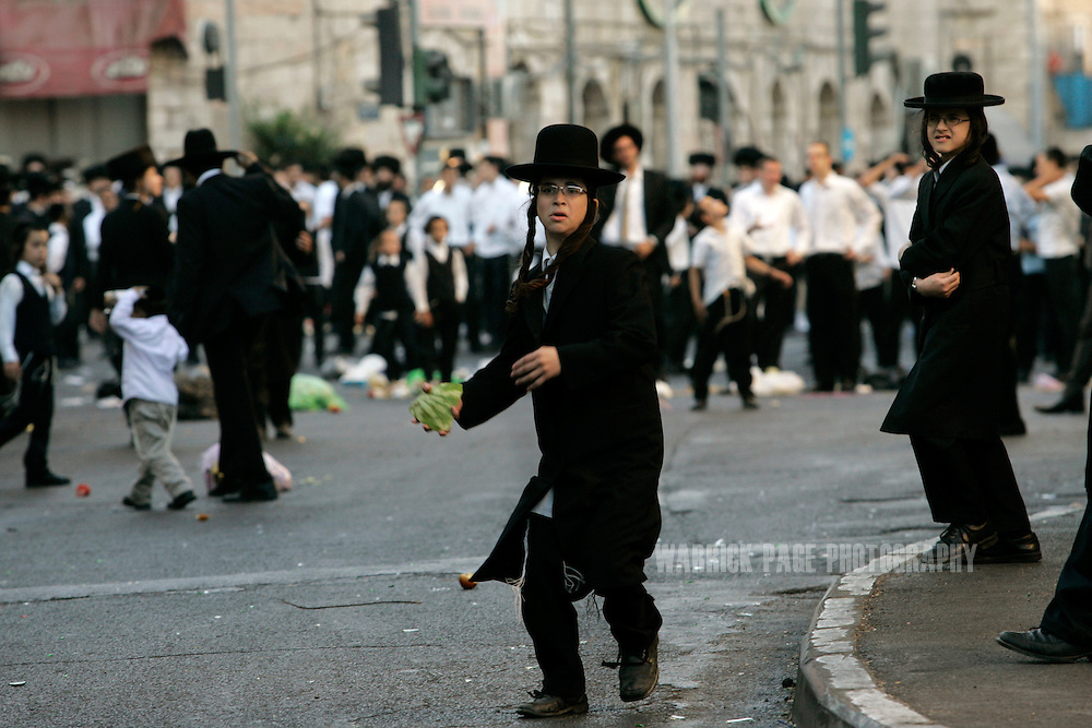 JERUSALEM, ISRAEL - JUNE 27: A young ultra orthodox Jew prepares to throw rotten fruit at police and media during a demonstration on Saturday, 27 June, 2009, in Jerusalem, Israel. Hundreds of ultra-orthodox jews threw rocks, glass bottles and garbage at police who prevented them from reaching a municipal car park scheduled to be opened on Saturday. Conservative and orthodox Jews traditionally don't work, drive, or operate machinery on Saturdays (Sabbath). (Photo by Warrick Page)