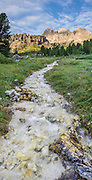 A stream flows from le Coronelle in the Rosengarten/Catinaccio group at sunrise in the Dolomites, Italy, Europe. From Pera di Fassa village (in Pozza di Fassa comune in Val di Fassa), in Trentino-Alto Adige/Südtirol region, Italy, take a bus or lift to visit Rifugio Gardeccia Hutte and hike in the Rosengarten mountain massif (Catinaccio Group) of the Dolomites. 200 million years ago, Triassic coral reefs fossilized into Dolomite. Collision of tectonic plates lifted the Dolomites within the Southern Limestone Alps. UNESCO honored the Dolomites as a natural World Heritage Site in 2009. This panorama was stitched from 9 overlapping photos.