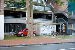 This small red car fits neatly behind a tree. The car is parked near the 'Beijneshal', a multi functional complex situated in front of the historic train station. The structure is one of the controversial development projects and is considered an eyesore by many locals.<br /> <br /> After living abroad for more than three years I visited my old home town. Wondering what has changed I packed both my curiosity and a camera. (Original posted as part of a photo essay 'Revisiting Familiar Grounds' here: http://www.basslabbers.com/WP/?p=1320)