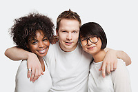 Portrait of young Caucasian man with his arms around two female friends over white background