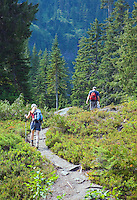Two hikers on forest trail in Cascade Mountains Washington USA.