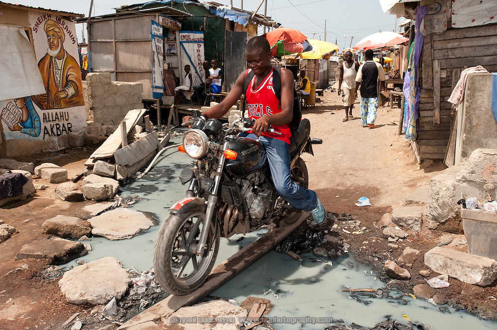 A man guides his motorcycle across a makeshift bridge in Old Fadama. Located in Ghana's capital Accra and colloquially referred to as 'Sodom and Gomorrah', Old Fadama is Ghana's largest slum and is home to some 80 000 people. With no public sanitation services at all, what limited toilet facilities exist in the community are privately owned and operate on a pay-per-use basis. People who cannot pay - children, for example - defecate in the open or in plastic bags which are often dumped near toilets, such as the one past which this drain flows.