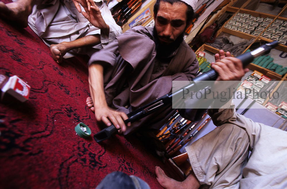 Kabul, 14 August 2005...A local shopkeeper sells Pakistani shotguns and ammunition...
