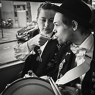 Young woman gives her boyfriend a bite of Icecream on the bus as they head home from participating in the parade on 17th of May the National holiday of norway