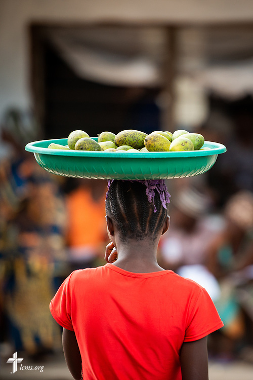 A woman sells fruit to waiting patients on the fourth day of the LCMS Mercy Medical Team on Thursday, May 10, 2018, in the Yardu village outside Koidu, Sierra Leone, West Africa. LCMS Communications/Erik M. Lunsford