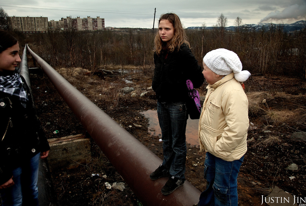 Girls stand on hot-water pipes in Zapolyarny, a town built for its nickel mining combine. Sulphur dioxide emitted from the factory (in the background on the right) kills vegetation, pollutes ground water and causes asthma, especially among children.
