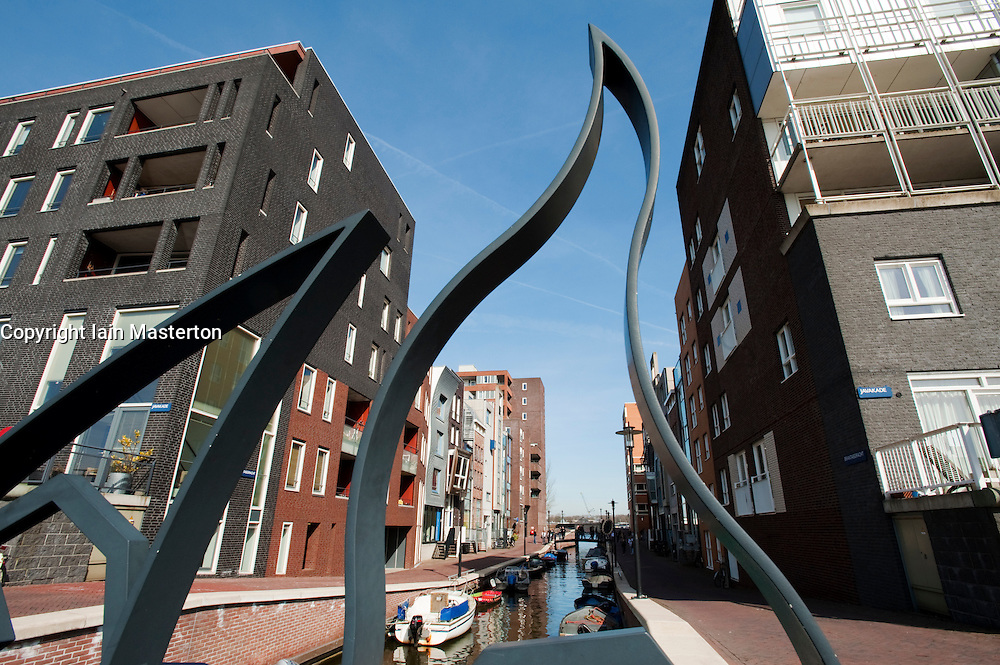 Canal and modern apartment buildings viewed through modern steel footbridge on Java Island new property development district in Amsterdam , The Netherlands