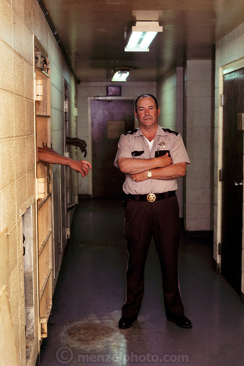 Sheriff Doris Weekly in his county jail, Ashland City, Tennessee, USA. The hands sticking out of the nearest cell belong to Johnny Walton, a neighbor of Menzel's who was serving time for theft. MODEL RELEASED.