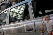 An ad on the side of a taxi cab with local architecture of the Square Mile, on 31st March 2017, in the City of London, England.