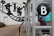 A bus passenger looks up the next service at Stop B alongside the film industry being celebrated outside Elstree and Borehamwood train station, on 15th October 2019, in London, England.