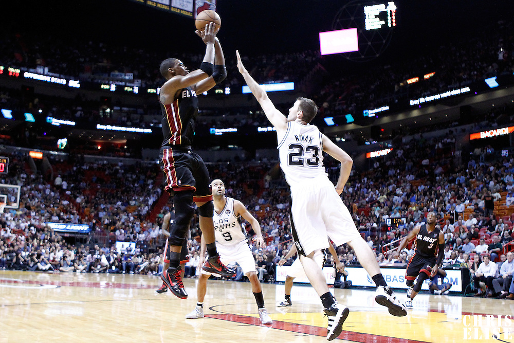 14 March 2011: Miami Heat power forward Chris Bosh (1) takes a jumpshot over San Antonio Spurs small forward Steve Novak (23) during the Miami Heat 110-80 victory over the San Antonio Spurs at the AmericanAirlines Arena, Miami, Florida, USA.