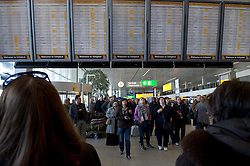 Passengers stranded by the ash cloud from a volcanic eruption in Iceland, look at the list of cancelled flights at Schiphol Airport in Amsterdam, the Netherlands, on Tuesday, April 20, 2010. (Photo © Jock Fistick)