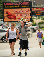 Visitors walk up from Weirs Beach to the Lobster Pound Restaurant and Bar.  (Karen Bobotas/for the Laconia Daily Sun)
