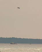 A Coast Guard helicopter circles after directing rescue boats to a woman who either fell or jumped from the Mackinaw Bridge.