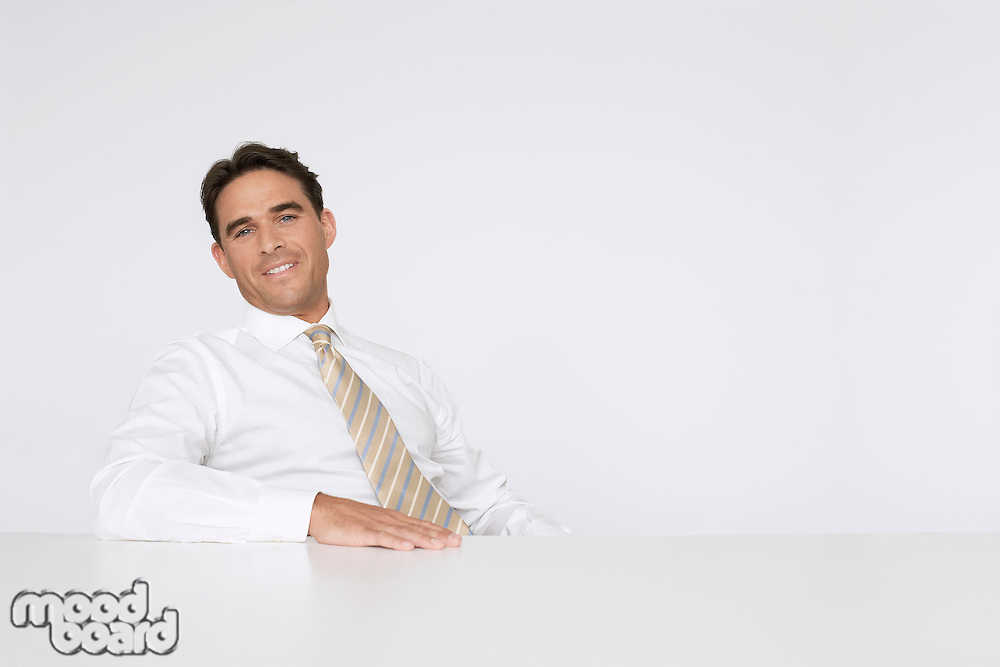 Businessman Sitting at White Table