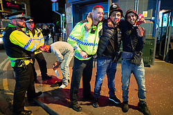 © Licensed to London News Pictures. 16/06/2018. Manchester, UK. People pose with police officers during celebrations of Eid-ul-Fitr , the end of a month of fasting during Ramadan , in Rusholme in Manchester . Photo credit: Joel Goodman/LNP