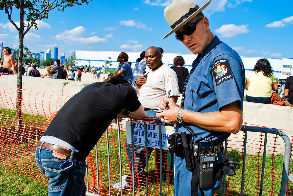 A New York State Park policeman pauses  as he writes a citation for an intoxicated Pool Partier at the JELLY Pool Party free concert series East River State Park, Brooklyn, New York, 2009