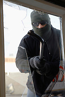 Masked thief braking glass with crowbar