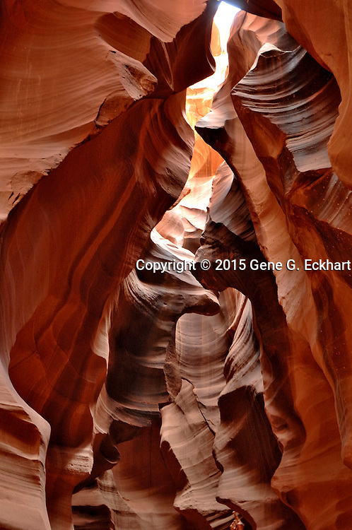 """The Navajo name for Upper Antelope Canyon is Tsé bighánílíní, which means """"the place where water runs through rocks."""" Antelope Canyon was formed by erosion of Navajo Sandstone, primarily due to flash flooding and secondarily due to other sub-aerial processes. Rainwater, especially during monsoon season, runs into the extensive basin above the slot canyon sections, picking up speed and sand as it rushes into the narrow passageways. Over time the passageways eroded away, making the corridors deeper and smoothing hard edges in such a way as to form characteristic 'flowing' shapes in the rock."""