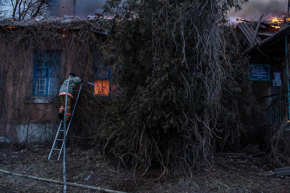 ARTEMIVSK, UKRAINE - FEBRUARY 14: A firefighter battles a blaze at a medical clinic which was hit by artillery on February 14, 2015 in Artemivsk, Ukraine. The clinic was closed and there were no reported casualties. A ceasefire between Ukrainian forces and pro-Russian rebels is scheduled to go into effect at midnight. (Photo by Brendan Hoffman/Getty Images) *** Local Caption ***