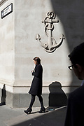 City workers walk through Lombard Street EC3 and beneath the carving of an anchor on a corporate office wall, in the heart of the capital's financial district, on 19th April, in the City of London, England.