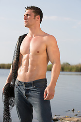 sexy muscular man with a fishing net in The Florida Everglades
