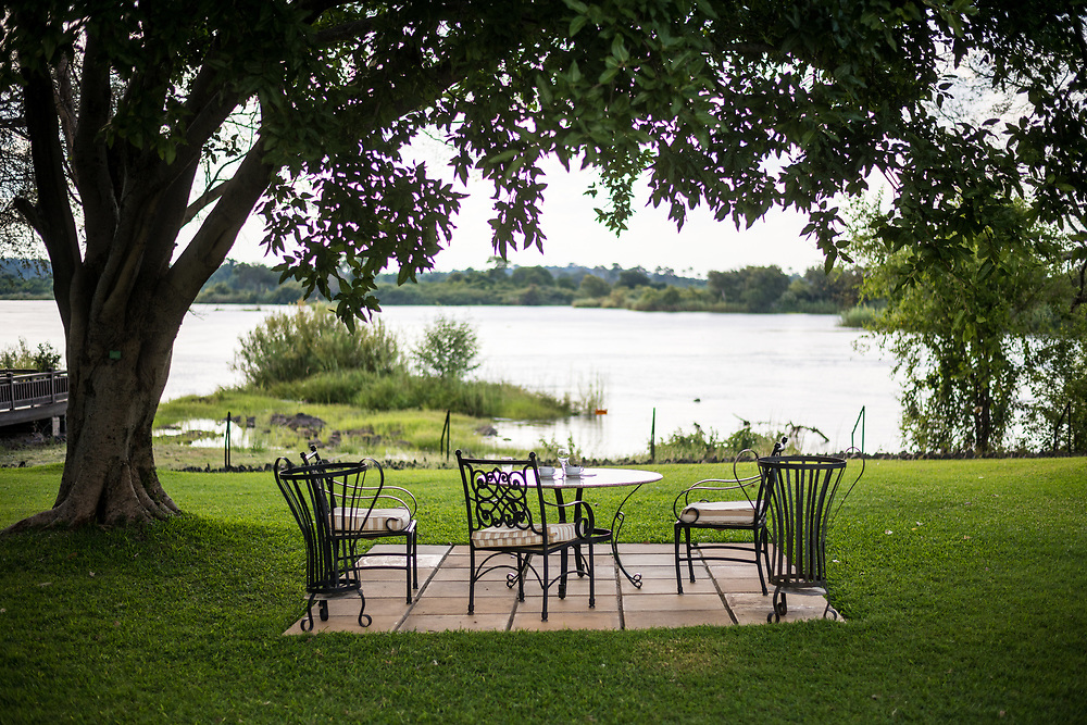 A table setup overlooks picturesque view of the Zambezi River at the Royal Livingston Hotel in Livingstone, Zambia