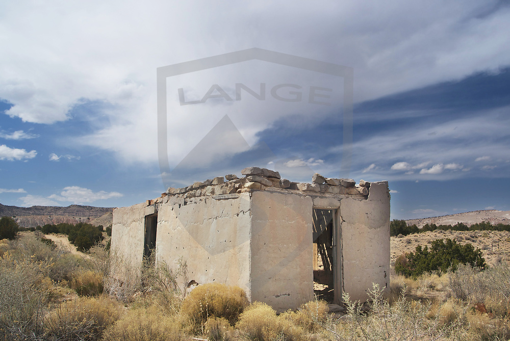 adobe ruin building against cloud filled blue sky and desert landscape at white mesa near the town of san ysidro, new mexico.
