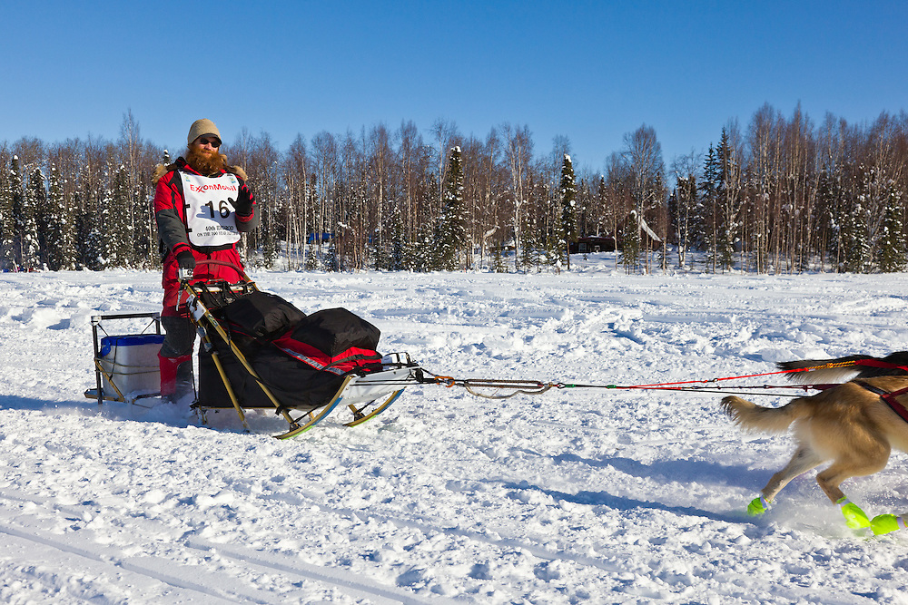 Musher Trent Herbst competing in the 40th Iditarod Trail Sled Dog Race on Long Lake after leaving the Willow Lake area at the restart in Southcentral Alaska. Afternoon. Winter.
