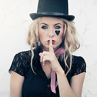 close up of a young woman with blonde hair wearing a top-hat