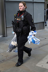 "© Licensed to London News Pictures. 25/10/2018. London, UK. A police Officer carrying Alain Robert's belongings after French ""Spiderman"" climbed London's Heron Tower near Liverpool Street Station. Photo credit: Dinendra Haria/LNP"