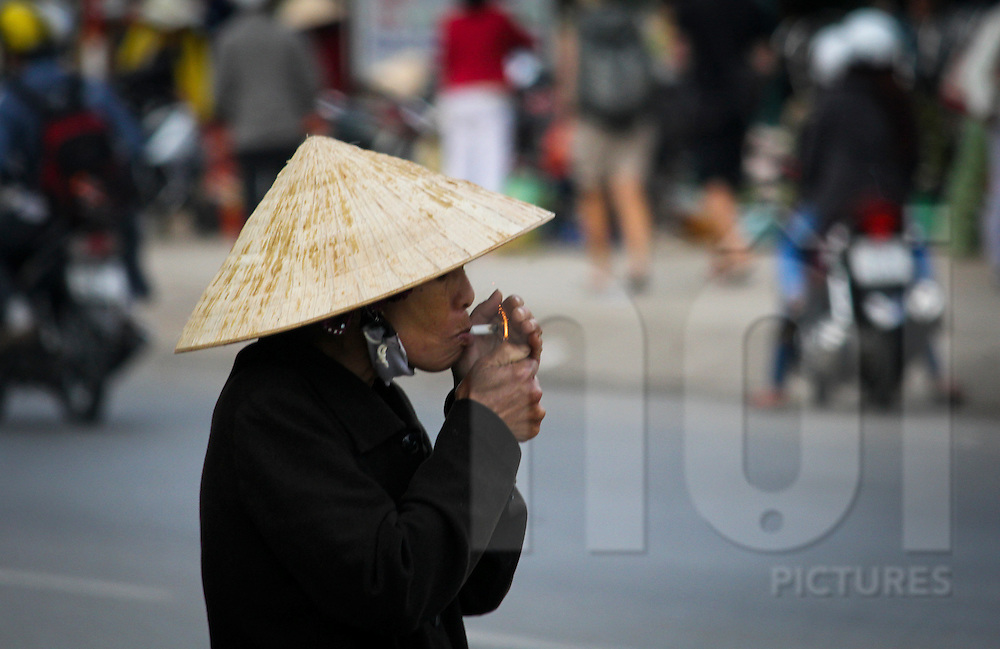 An elderly woman wearing a conical hat lights her cigarette, Dalat, Lam Dong Province, Vietnam, Southeast Asia
