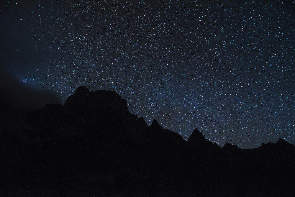 The silhouette of the peaks of Mt. Kenya are framed by the vibrant stars of the Milky Way galaxy.
