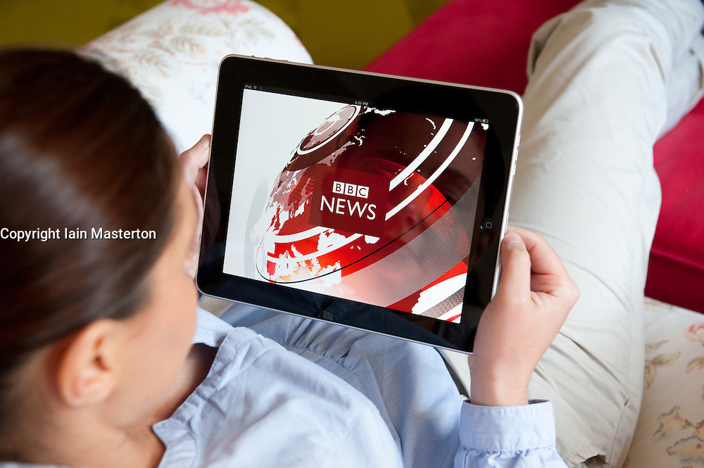 Woman using iPad tablet computer to read world news on BBC News application