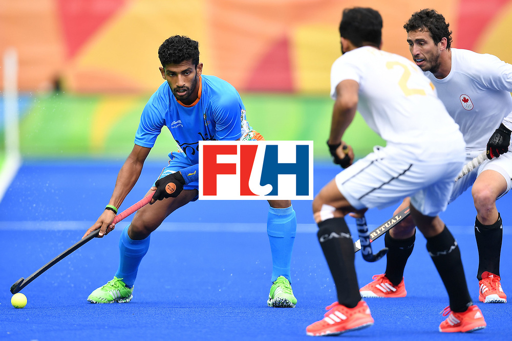 India's Uthappa Sannuvanda (L) and Canada's Sukhi Panesar (C) vie for the ball during the mens's field hockey India vs Canada match of the Rio 2016 Olympics Games at the Olympic Hockey Centre in Rio de Janeiro on August, 12 2016. / AFP / MANAN VATSYAYANA        (Photo credit should read MANAN VATSYAYANA/AFP/Getty Images)
