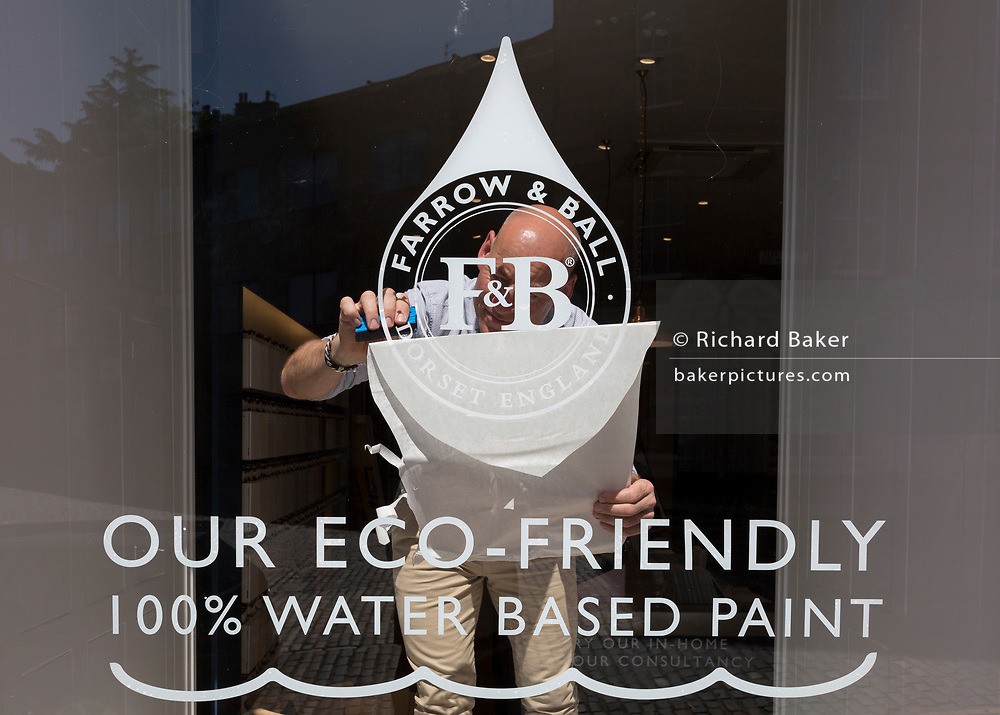 Unpeeling and sticking a window stencil to the glass of eco paint retailer Farrow & Ball, in Edinburgh, on 26th June 2019, in Edinburgh, Scotland.
