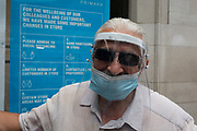 "In the 24hrs that a further 38 died from Coronavirus, bringing the total to 41,736, a further easing of the UK's Covid pandemic lockdown restrictions took place with many high street shops today being allowed to re-open after three months of forced closure. Prime Minister Boris Johnson, wanting to stimulate the economy, has urged people to ""shop with confidence"" and long queues formed outside the main brands. But unlike on public transport, face coverings are not compulsory so shop floors and shopping practices have had to be adapted to ensure customers' social distances, amid fears of a second infection wave. A portrait of a shopper wearing a face shield that has eyelashes drawn on to the plastic visor, outside Primark on Oxford Street, on 15th June 2020, in London, England."