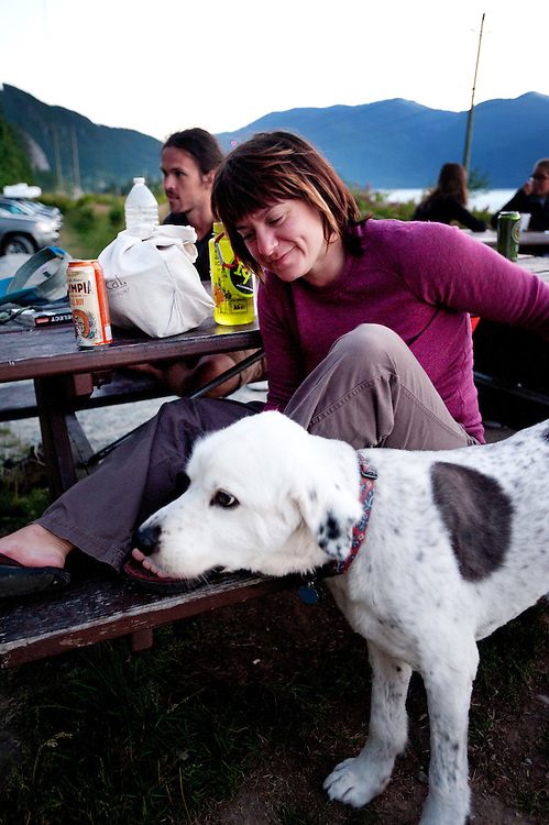 Climber Jennifer Nichols, rom Bellingham Washington, pets her dog Moby after a day of climbing on the Stawamus Chief.<br /> <br /> Life along the Stawamus Chief Provincial Park campsite, also known as the Squamish Climber's Campground, where climber's from all over the world come stay while climbing in Squamish.<br /> <br /> Photo Credit: David Buzzard