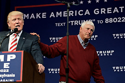 Retired basketball coach Robert Knight puts a hand on the shoulder of Donald Trump after introducing Republican presidential nominee on stage at a. Rally in Aston, Pennsylvania.