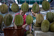 A customer (right) orders some durians at a roadside stall during the Durian Festival in Georgetown, Pulau Pinang, Malaysia on June 16th, 2019. The tropical fruit has become one of China's latest culinary fixations, sending the export demand and prices soaring, and becoming a point of attraction for tourists who come to Malaysia to try its famed varieties.  Photo by Suzanne Lee/PANOS for Los Angeles Times
