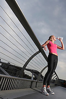 Woman standing on foot bridge drinking water from bottle low angle view Millennium Bridge London England
