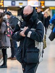 © Licensed to London News Pictures. 05/03/2020. London, UK. A man at Victoria Station heads to work wrapped up and wearing a mask as the Government announces plans to combat the coronavirus disease crisis. Photo credit: Alex Lentati/LNP