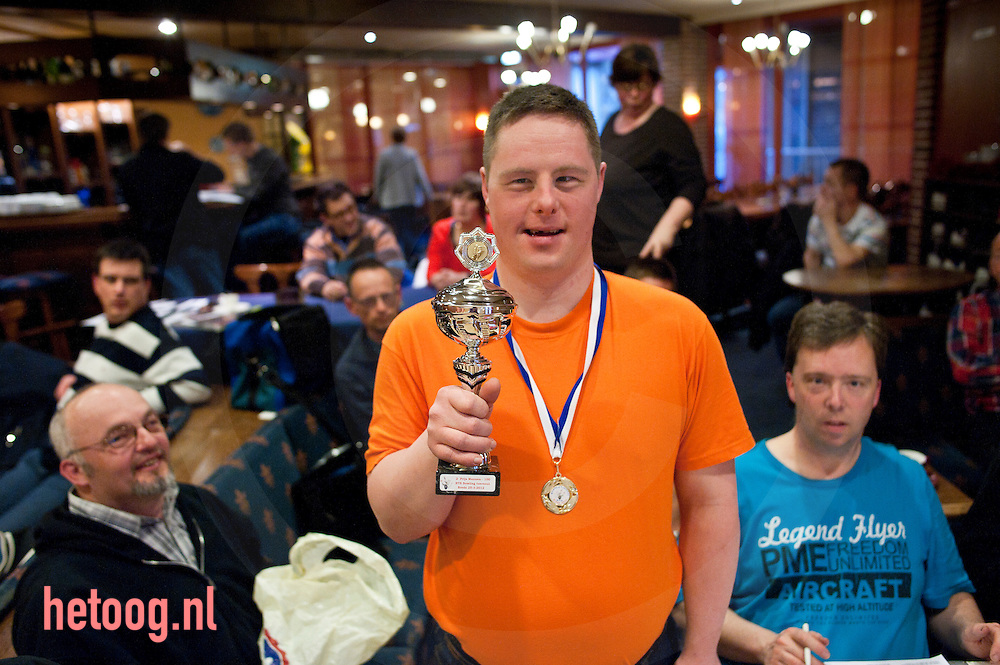 """nederland, deuringen 04april2012 Een Bowler toont zijn onlangs  gewonnen prijs (nationaal toernooi in Breda) bowlen voor verstandelijk gehandicapten in zaal 'Golbach"""" in deurningen."""